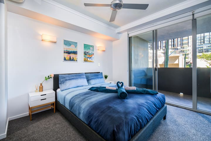 Master bedroom with queen bed, deluxe mattress, air-conditioning, walk-in robe, luxe ensuite and balcony access.