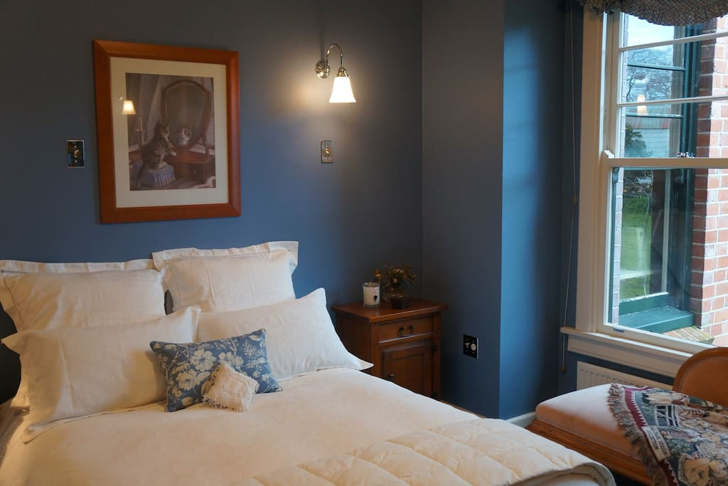 The Classic Guest Room has a double bed, chaise lounge and antique dresser.
