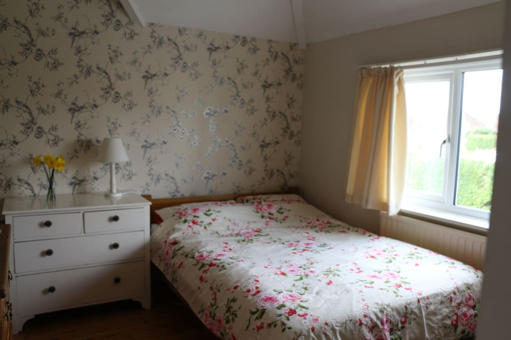 Guest double bedroom with hardwood floors, drawers and built in wardrobe.