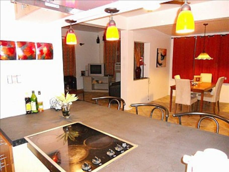 Open plan apartment, view from kitchen to breakfast bar to living room to dining room