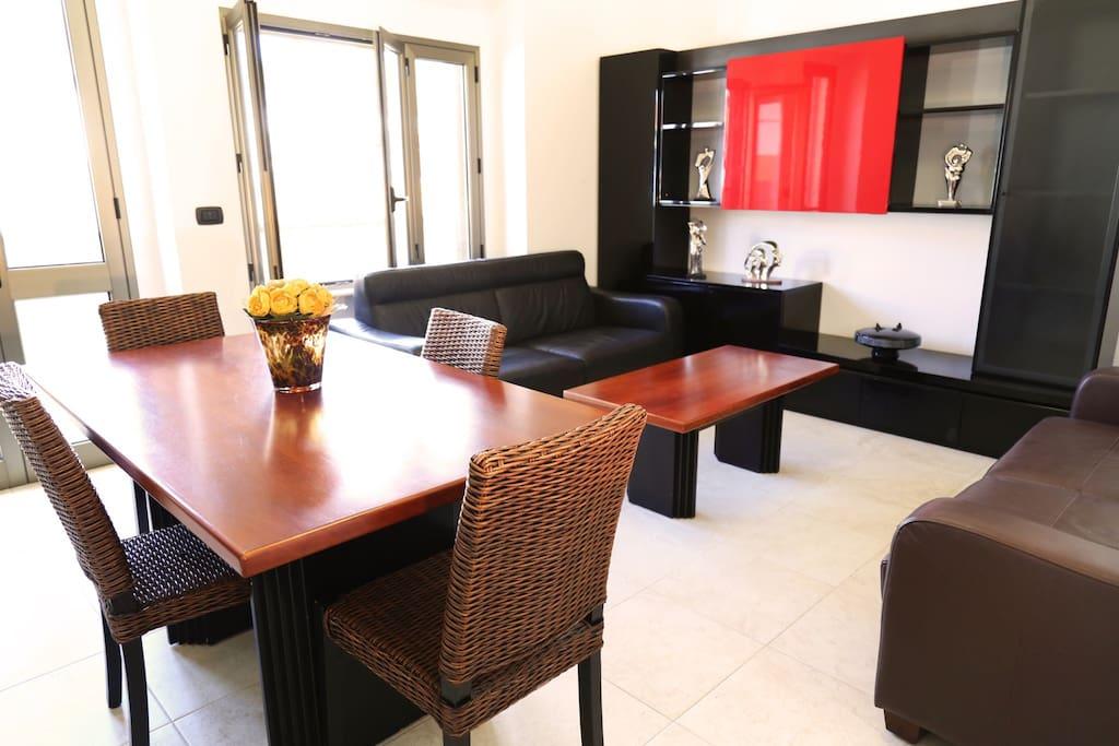 Sala da pranzo e soggiorno attrezzati con tavolo, TV, divani letto matrimoniali, balcone, condizionatore