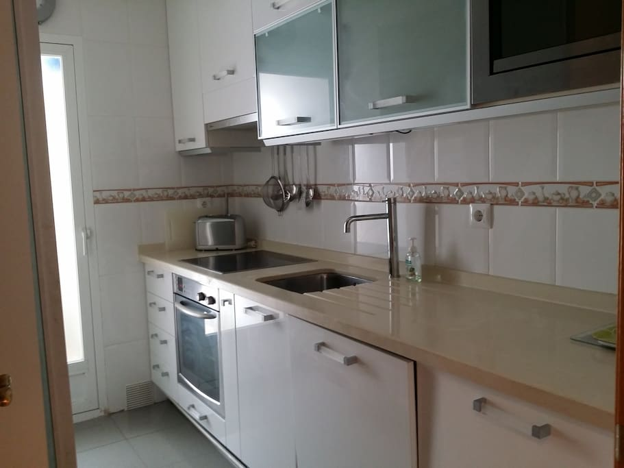 Fitted kitchen with dish washer, oven and door to utility room