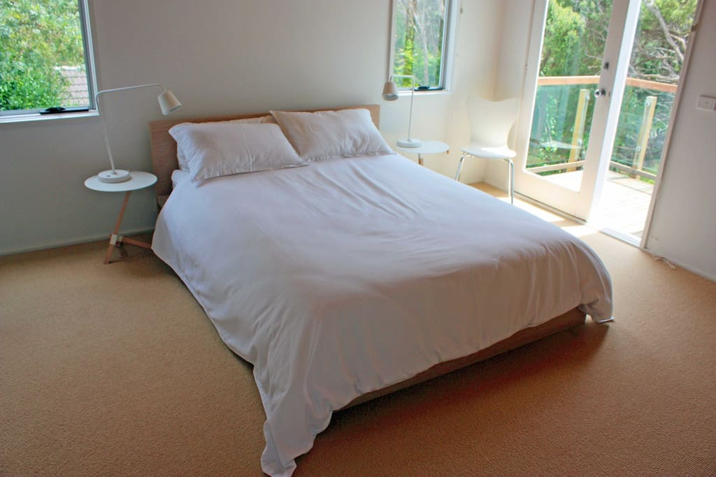 The spacious main bedroom has a small adjoining balcony and an ensuite bathroom.