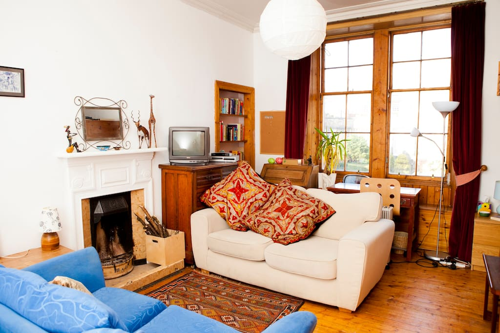 Sitting Room with open fire, high ceiling and large original Sash & Case windows.