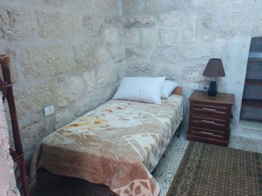 This is one of the beds in the first room. Notice the limestone wall. Shelves on the left and right.