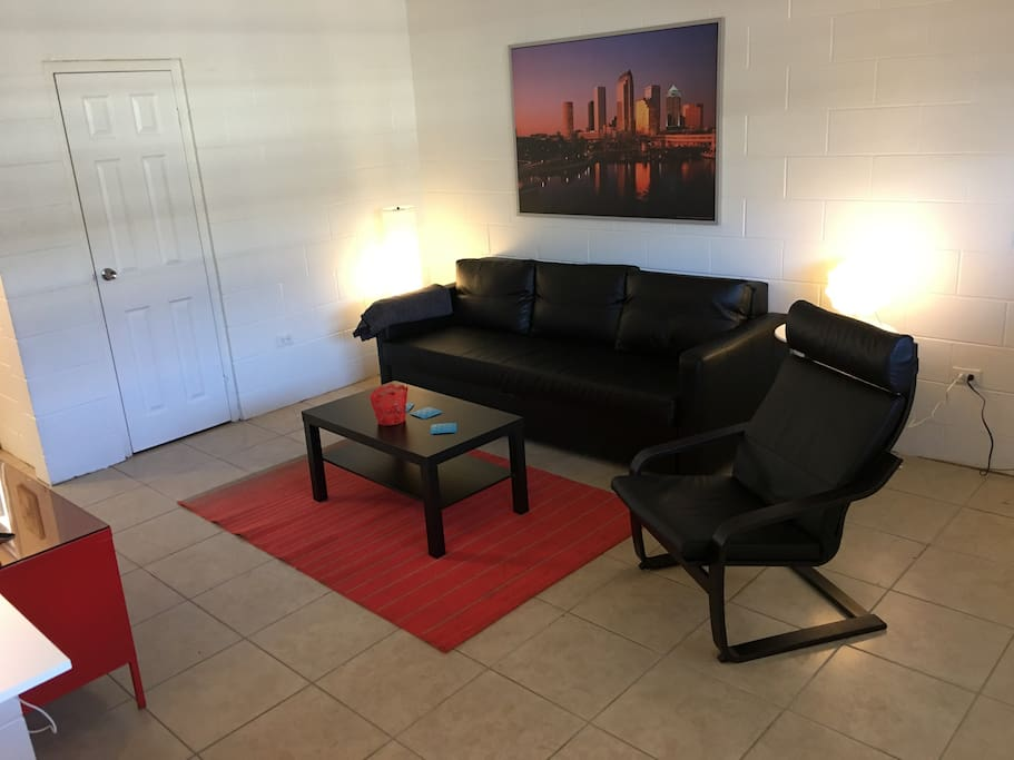 The livingroom is furnished with a leather sleeper sofa and accompying leather chair