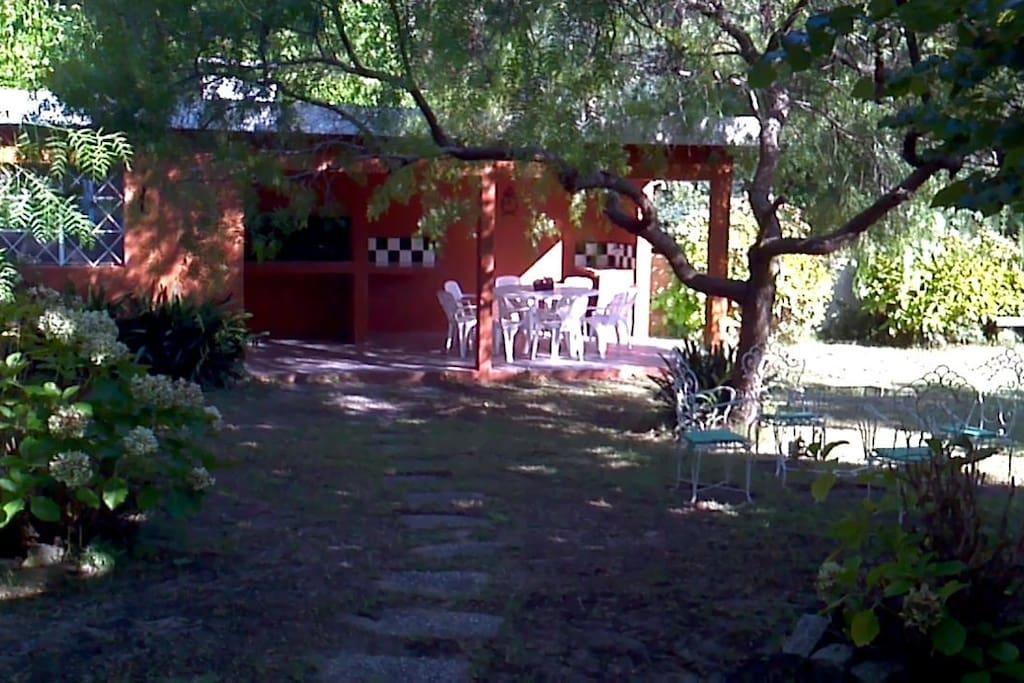Fondo arbolado con parrillero techado y mesa para 8 personas