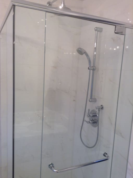 The bath has a separate glass shower stall
