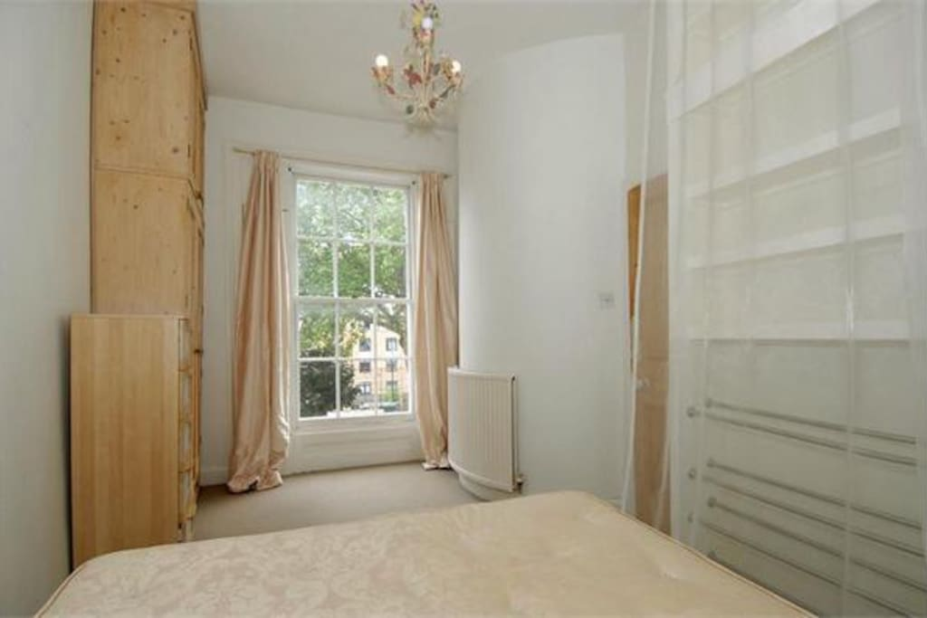 Large sunny bedroom with comfortable new king bed (bedding not shown but is provided)