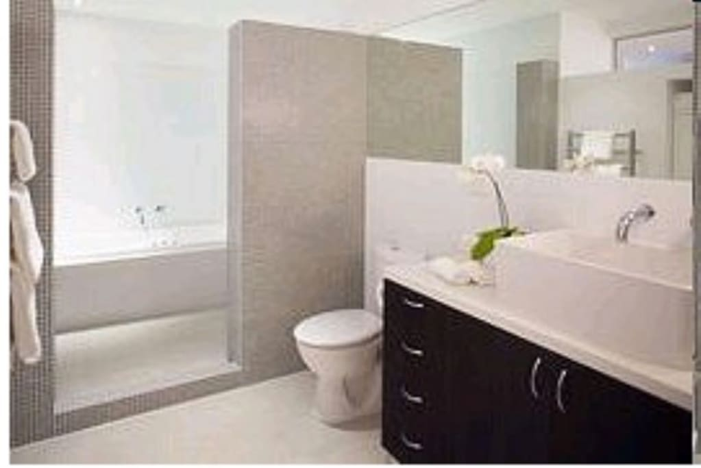 Spacious bathroom with shower, spa bath and plenty of cupboard space