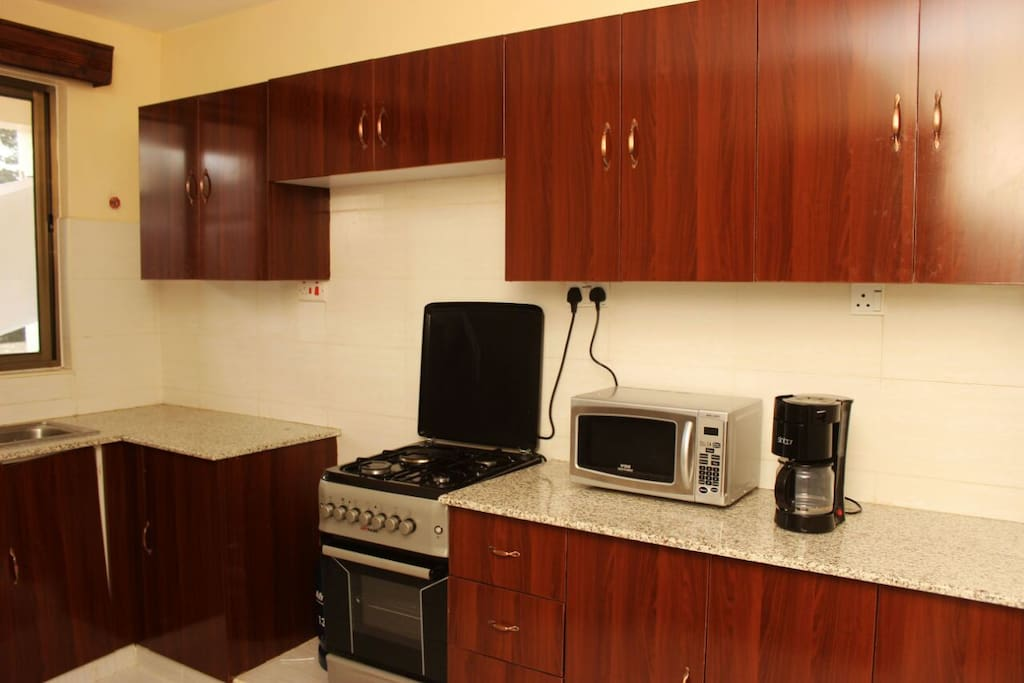modern kitchen with microwave coffee make coocer and fridge