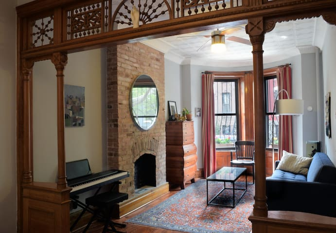 The living room looks out onto a beautiful northern Park Slope block.