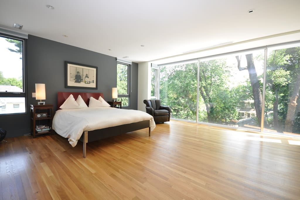 Master bedroom with queen-size bed and floor-to-ceiling windows.
