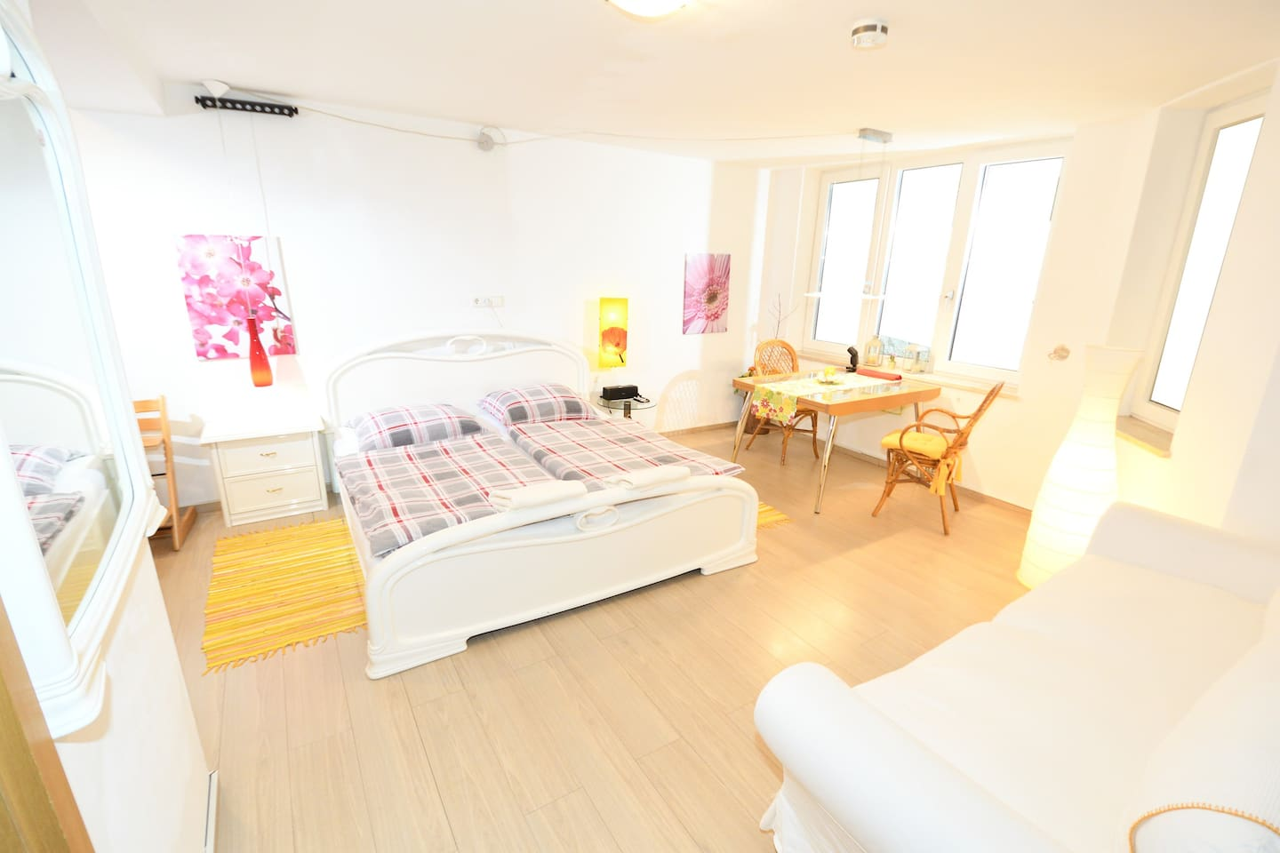 Helles Souterrainzimmer mit Doppelbett, Tisch und Sofa /  / Bright basement room with double bed, table and sofa (2019)
