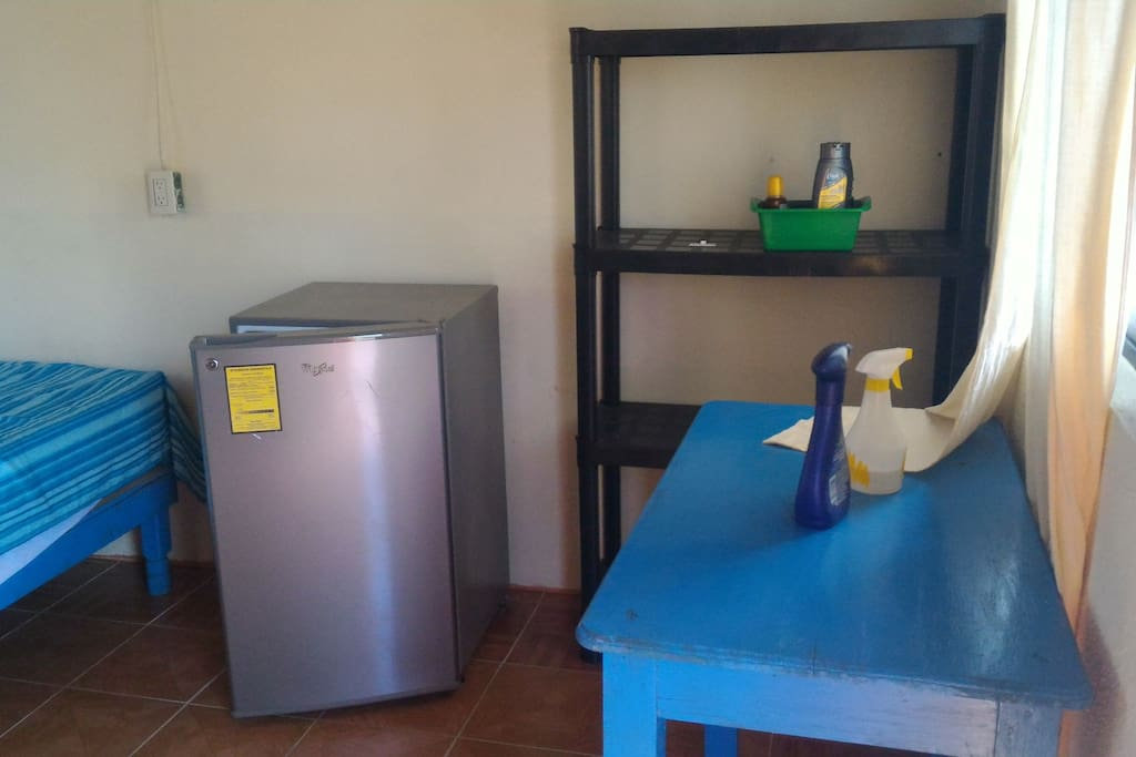 To the right of the door. Small fridge, shelves, table.