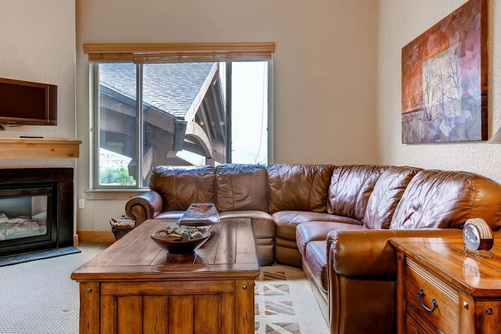 The living area features an oversized L-shaped leather sofa, a 32 inch television.