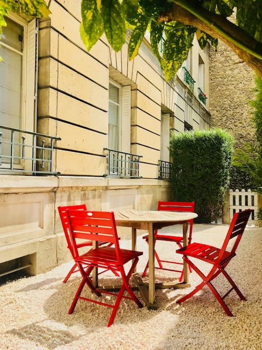 small garden with table and chairs, with the apartment