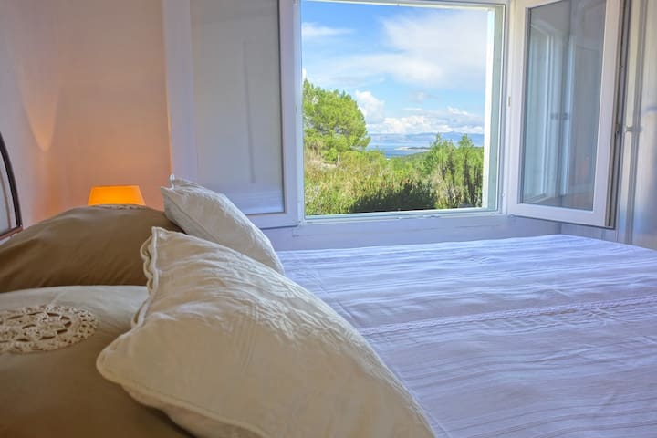 Bedroom 2, with a view over south eastern sea and lush surrounding greenery.