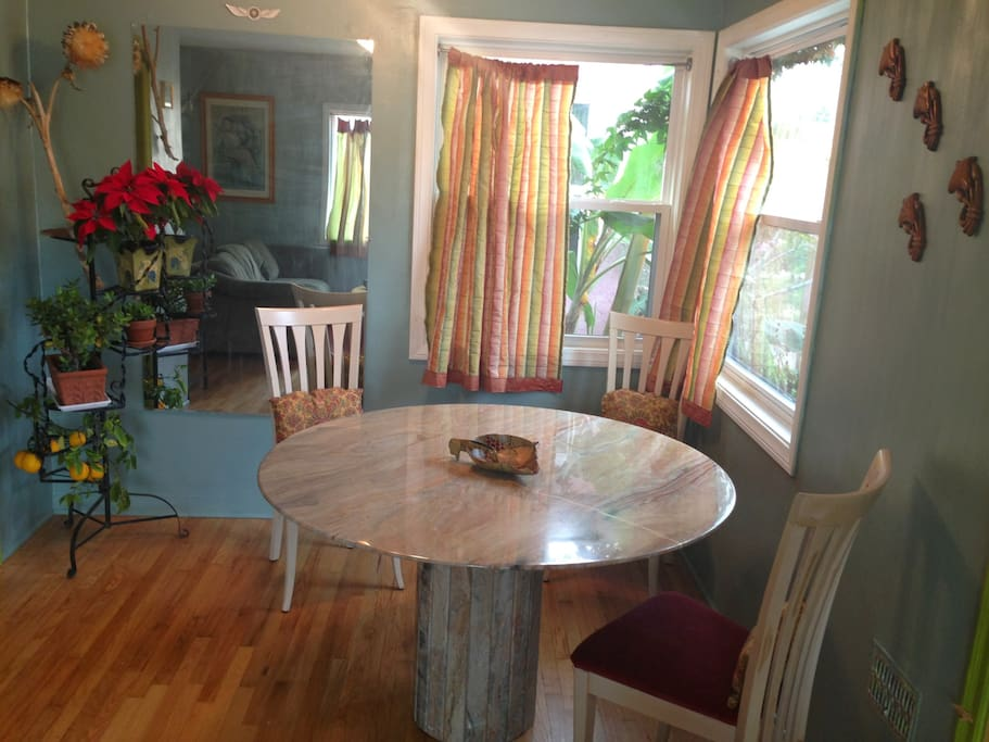 The bright and cheerful Italian marble dining area with Banana tree just outside the window!