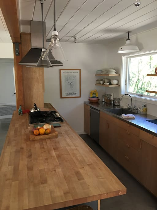 newly remodeled kitchen with butcher block and stainless steel countertops