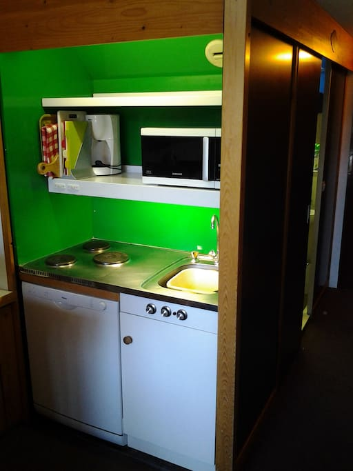 Compact kitchenette with crockery, cutlery, hob and microwave