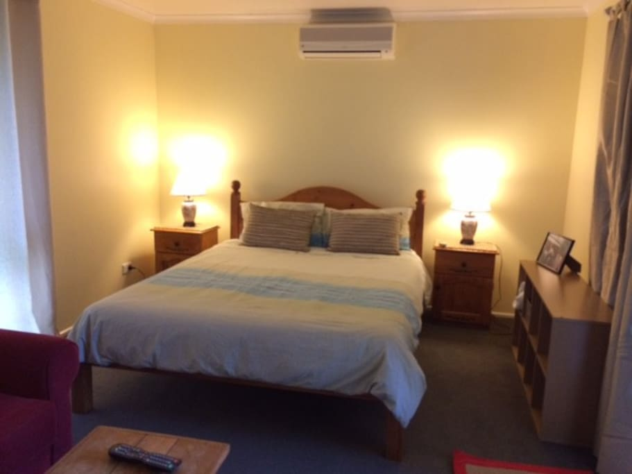 Air conditioned bedroom with Queen size bed and TV.