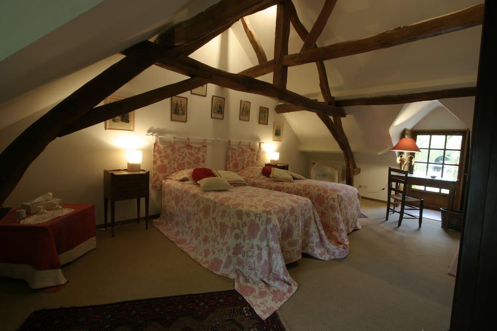 Chambre rose de la Suite : la chaleur des poutres apparentes. Le lit d'appoint peut être mis dans cette chambre.