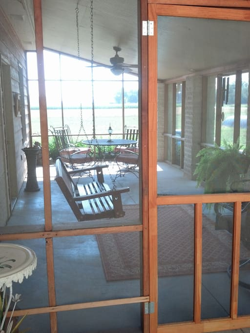Screened in porch with swing and sitting area.