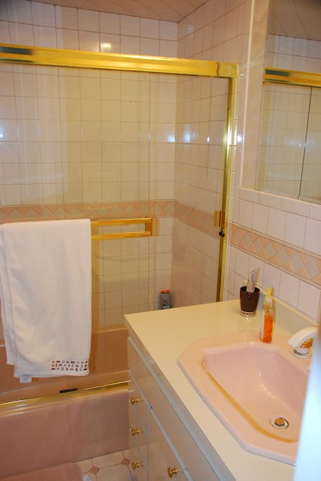 Clean bathroom with full tub and shower