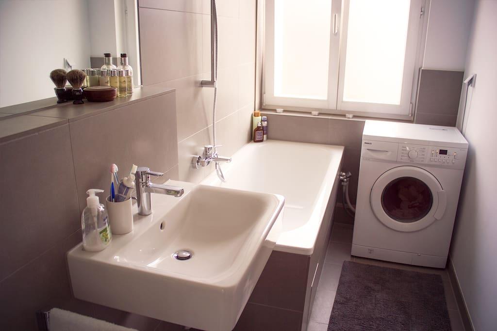 Bathroom with shower, bath tub, washing machine