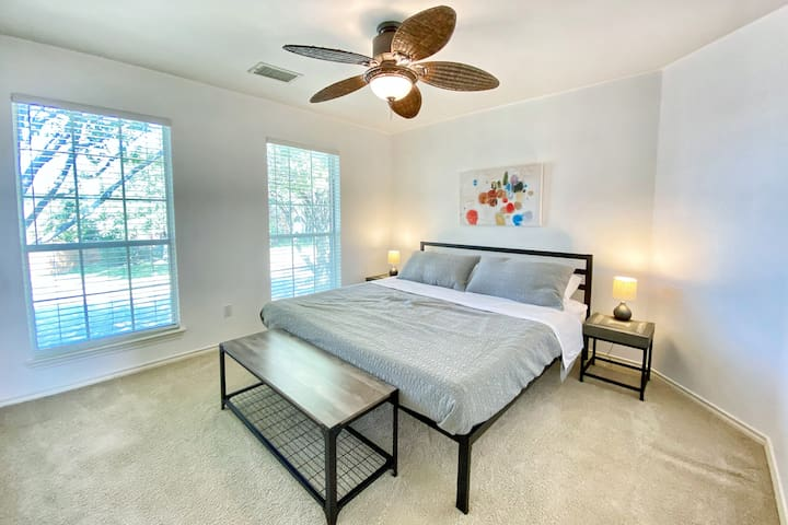 This room also features a king bed and two windows overlooking the tree-lined street outside.