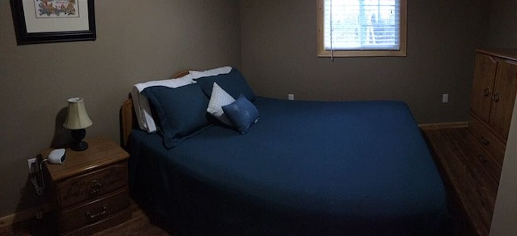 second bedroom with queen bed and one end table