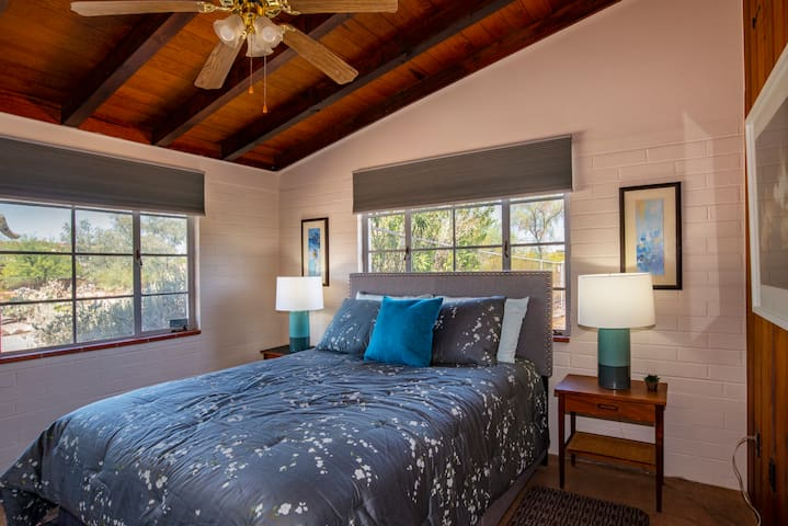 Bedroom with queen sized bed, end tables, lamps, ceiling fan and closet.