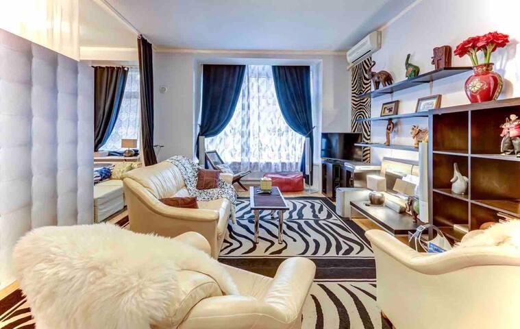Гостиная,комплект кожаной мебели для отдыха.Просторное, эркерное окно,широкий подоконник.Вид на  приватный двор с подсветкой и тихий скверик.Солнечная сторона.