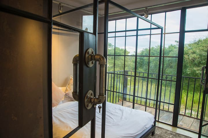 Bedroom 1 - with balcony overlooking lush landscape