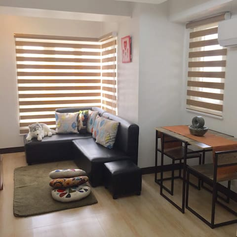 Living room with split-type aircon, LED flat screen TV w/ cable, telephone & dining table for 2.