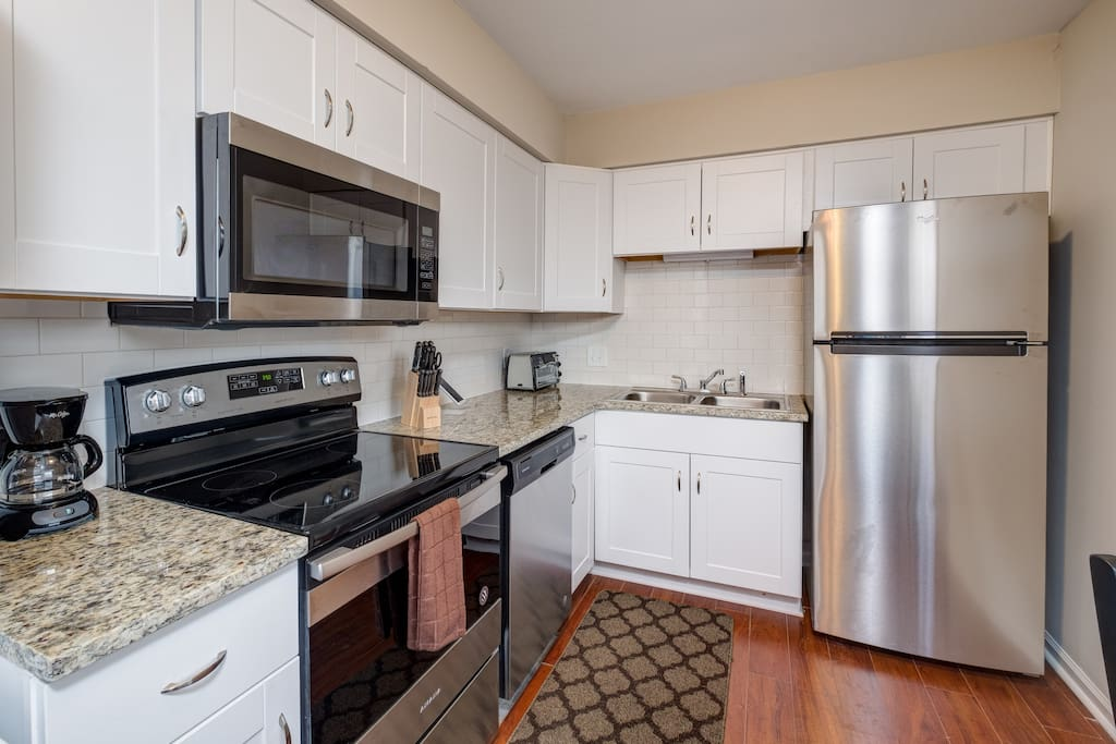 The kitchen boasts brand-new granite countertops, subway tile, and updated stainless steel appliances.