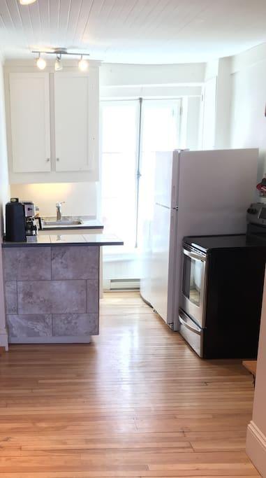 Bright kitchen. Coffee machine makes espresso and regular coffee.