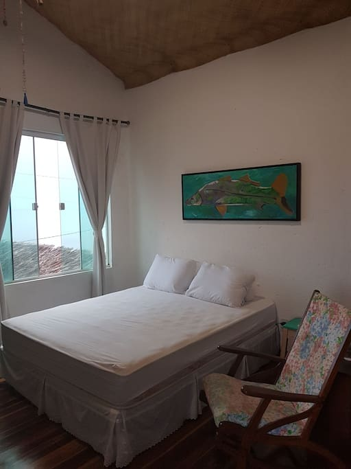 Quarto casal, da cama pode se ver o mar.