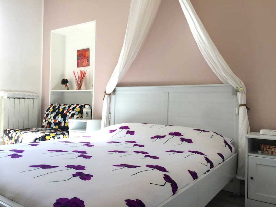 bedroom with double bed and one single bed ( chairbed), balcony