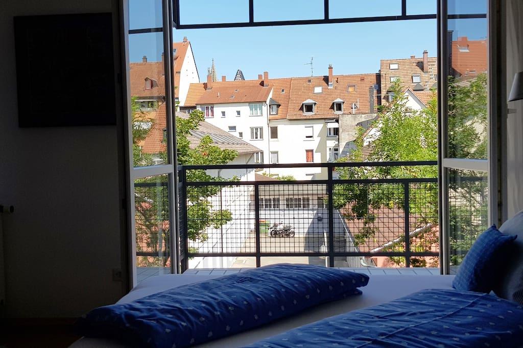 Blick vom Bett auf den hellen, ruhigen Innenhof. Morgens von der aufgehenden Sonne geweckt werden