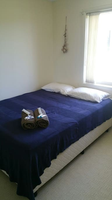 Queen bed with linen, towels, toiletries