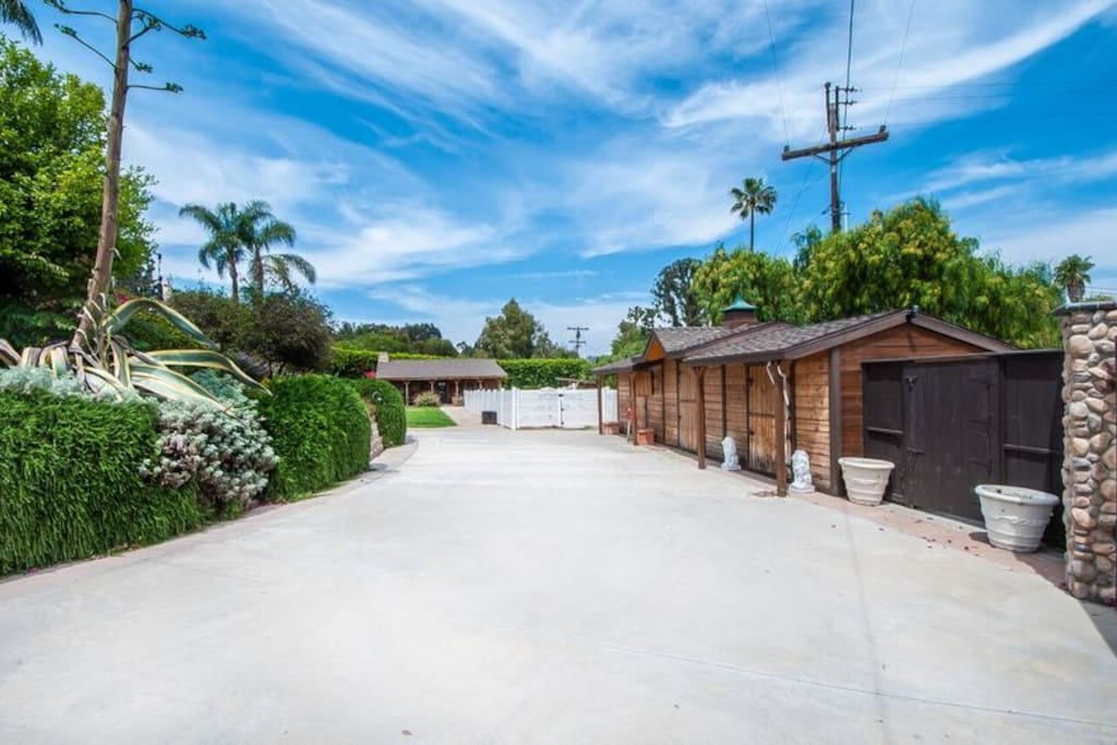 Large, gated driveway next to barns and horse arena.