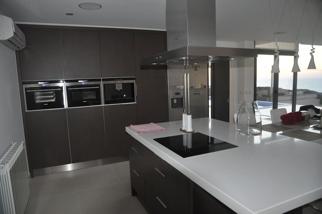 Keuken met inductie kookplaat, steamoven, combi-oven, espressomachine, Amerikaanse frigo.