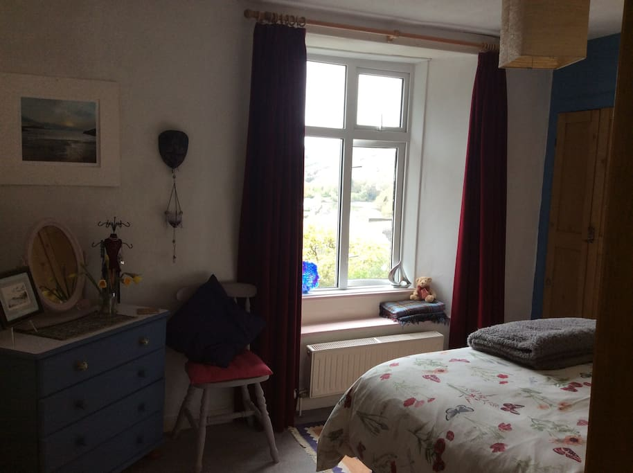 The bedroom looks over the river & woodlands