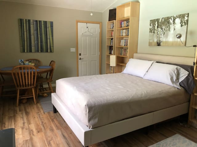 The first bedroom has the private entrance, dining table, queen bed, kitchenette and many books to read.