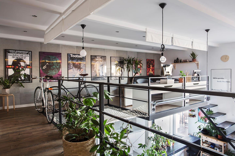 Na piętrze jest biuro z dwoma miejscami do pracy, sofą, siatką i galerią plakatów filmowych z Polskiej Szkoły Plakatu