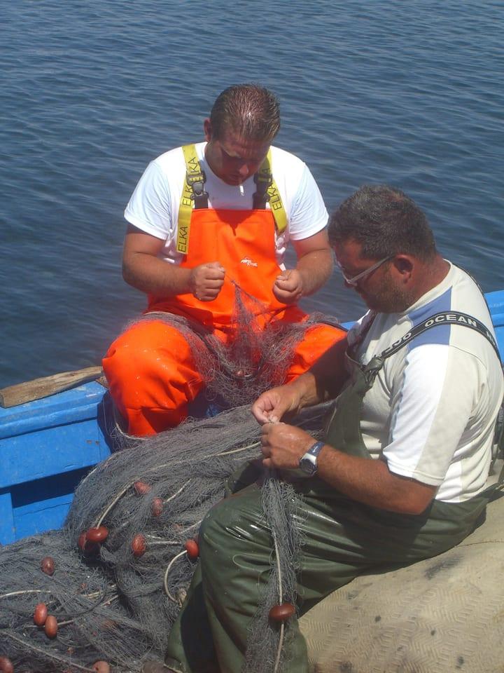 fishermen repairing their nets