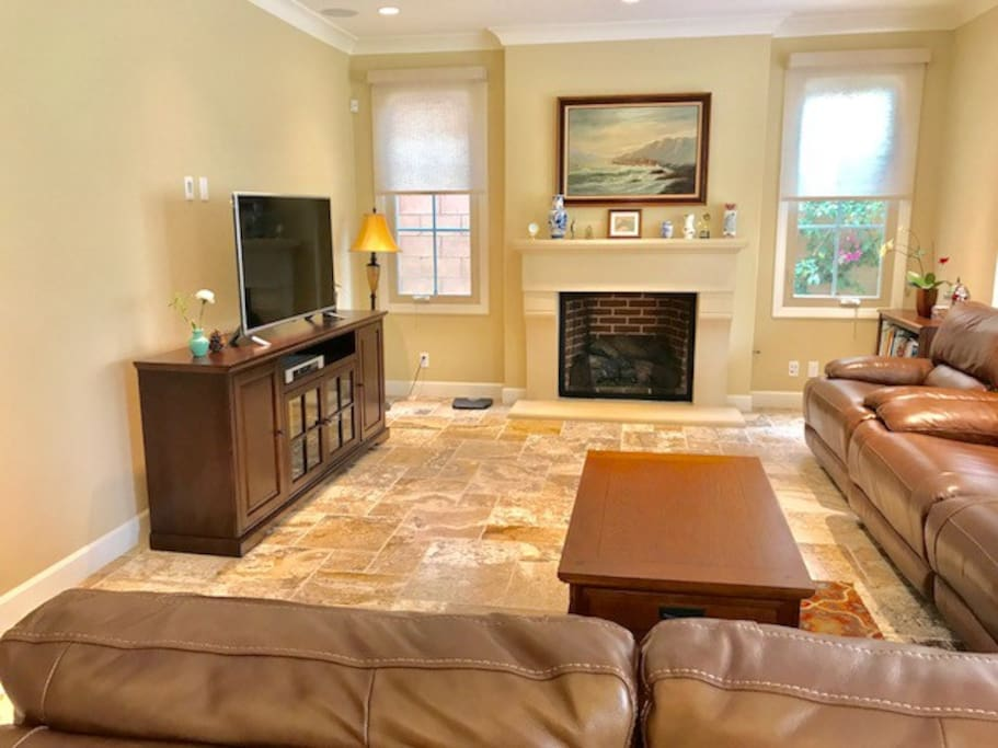 Spacious living room with big screen TV, comfy leather couch and fireplace.