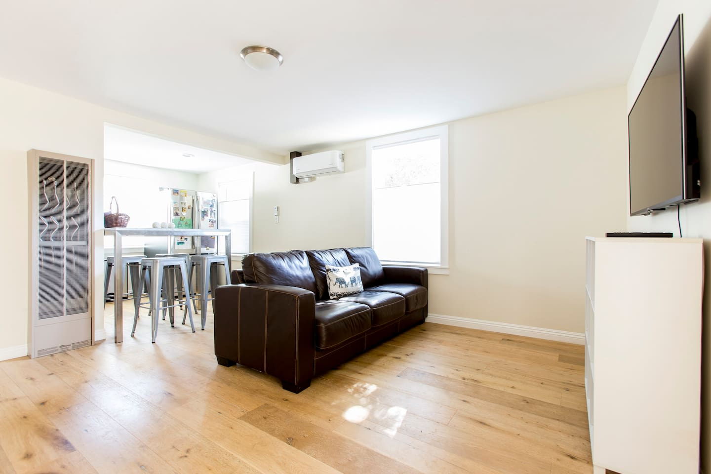 Our minimalist-designed living room features a comfy couch with Smart TV and DVD/Blue-Ray player and a welcoming breakfast bar, outfitted with ductless AC/Heat.